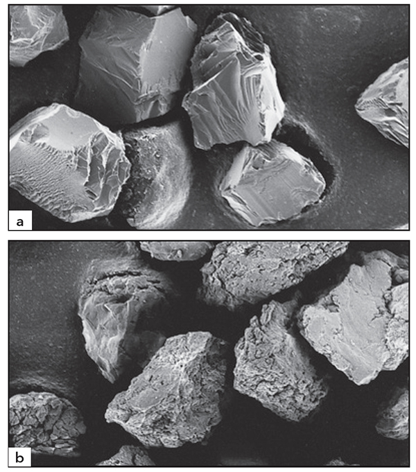 Figure 3.13 Comparison of monocrystaliline a) and polycrstalline b) synthetic diamond grain shapes (SEM, 450X)